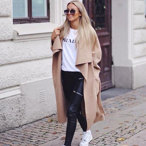 Девушка в кожаных леггинсах и бежевом пальто