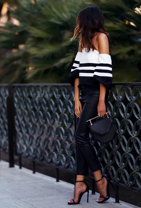 Девушка в кожаных штанах, черно-белой полосатой блузе, босоножки и сумочка
