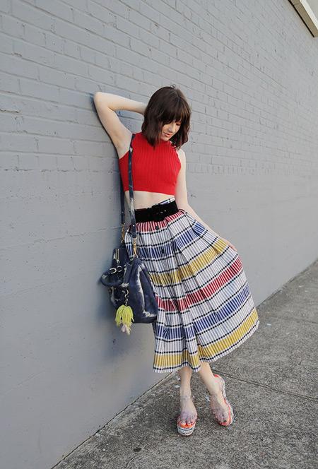 Девушка в красном кроп топе и полосатой разноцветной юбке миди