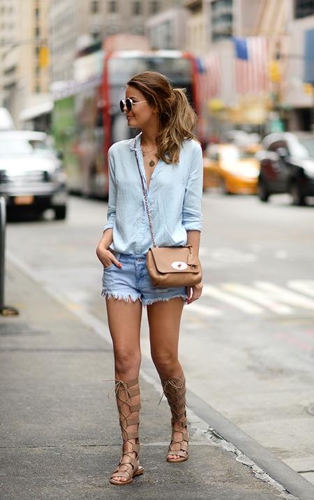 Девушка в мини шортах, голубой рубашке и бежевые сандалии гладиаторы