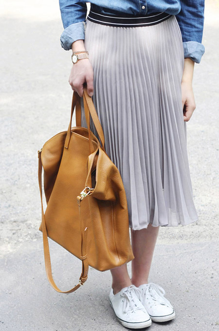 Девушка в плиссированной юбке, белых кедах и с сумкой тоут