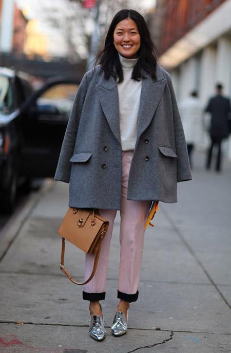 Девушка в розовых брюках и светлом пальто