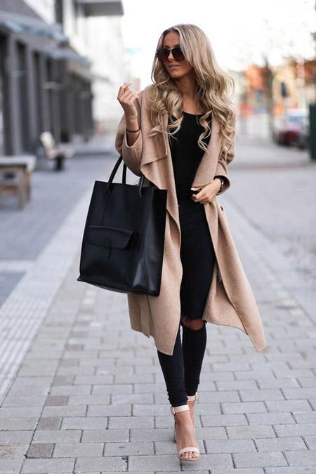 Девушка в рваных черных джинсах и длинном пальто