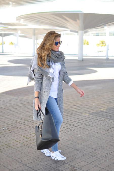 Девушка в сером пальто, голубых джинсах и черной сумкой тоут