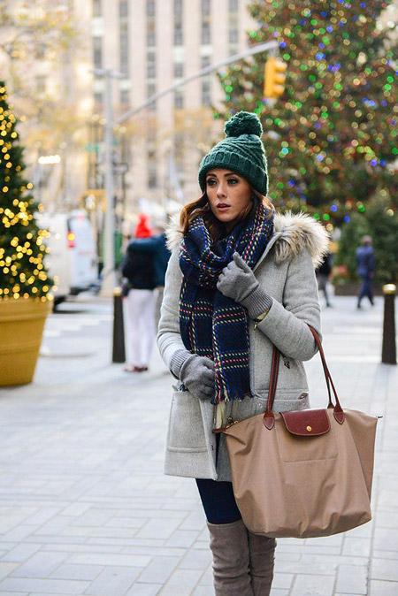 Девушка в сером пальто, зкленой шапке и с бежевой сумкой тоут