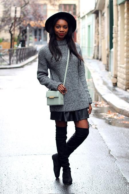 Девушка в сером свитере и кожаной юбке