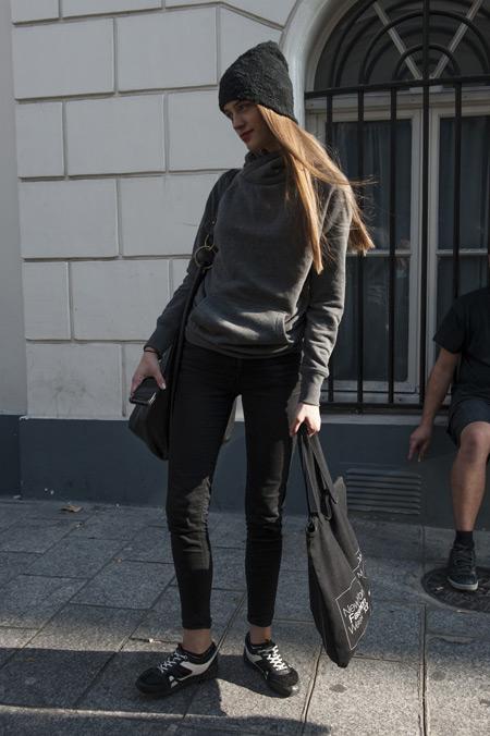Девушка в серых джинсах, олимпийка, шапка и черная сумка тоут