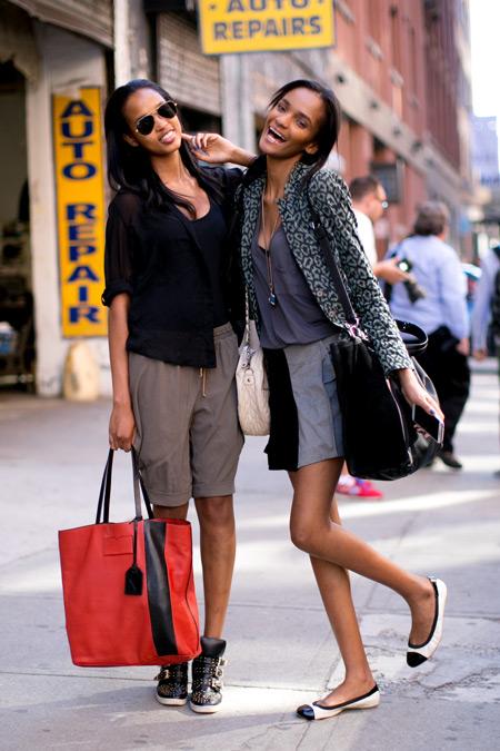 Девушка в шортах бермудах, черный топ и красная сумка тоут