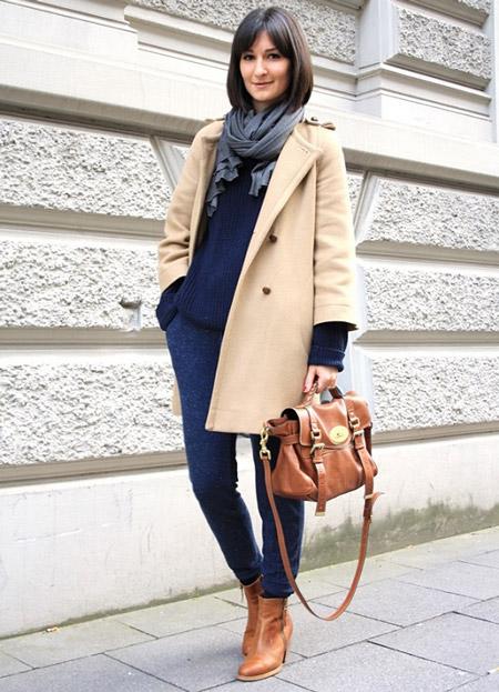 Девушка в синих брюках и бежевом пальто