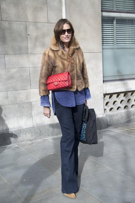 Девушка в синих брюках, меховая куртка, красная сумочка и черная сумка тоут