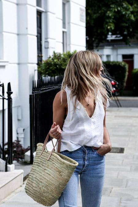 Девушка в синих джинсах, белом топе и с плетеной сумкой тоут