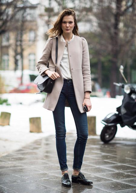 Девушка в узких джинсах и светлом пальто
