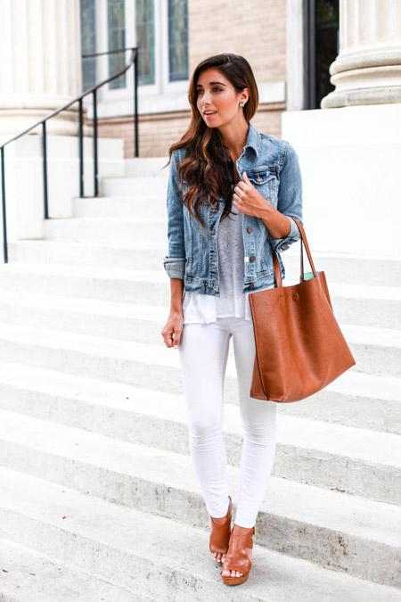 Девушка в в белых джинсах, синей джинсовке и с коричневой сумкой тоут
