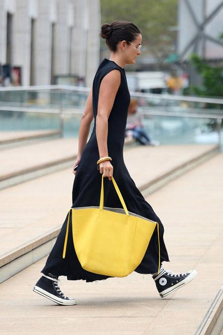 Девушка в в черном макси платье, кедах и с желтой сумкой тоут