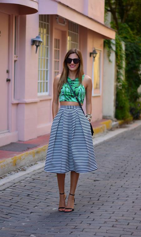 Девушка в зеленом кроп топе и полосатой юбке миди