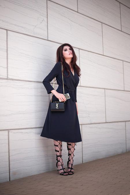 Мдель в черном платье миди, сумочка и сандалии гладиаторы