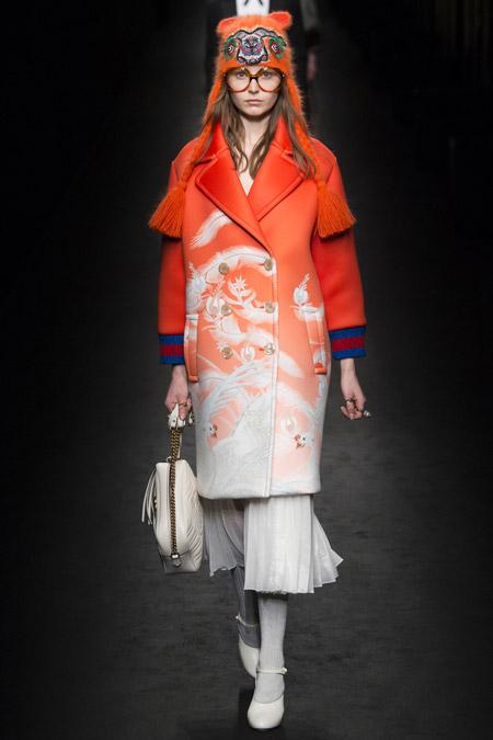 Модель на показе Gucci в оранжевой шапке с кисточками и принтом