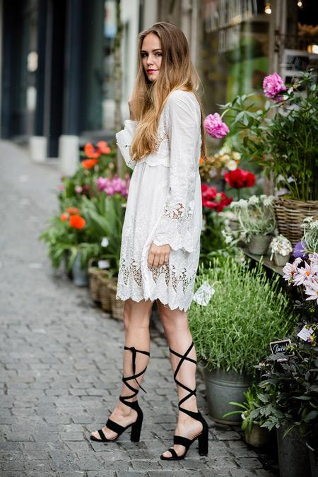 Модель в белом кружевном платье и черные сандалии гладиаторы