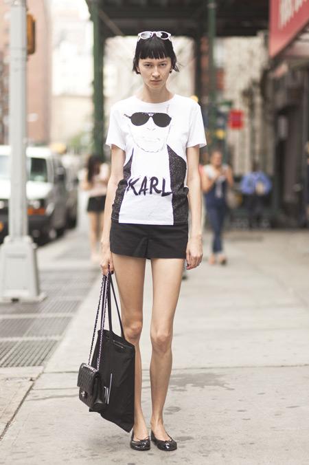 Модель в белой футболке с принтом, черные балетки и сумка тоут