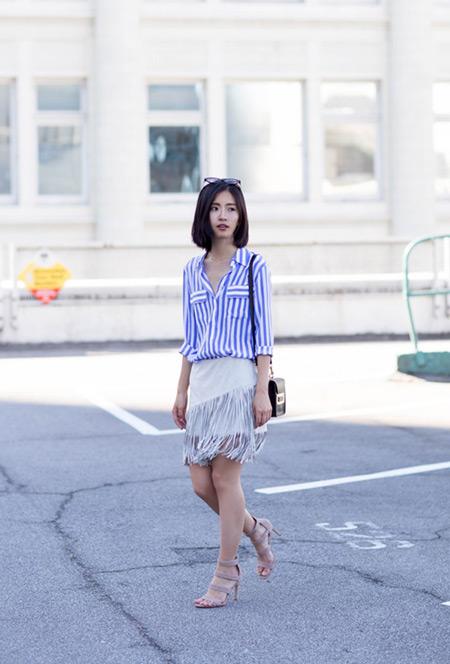 Модель в белой юбке и бело голубой полосатой рубашке