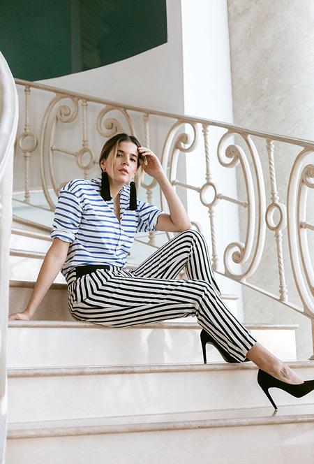 Модель в черно белых брюках в полоску и белой рубашке в синию горизонтальную полоску