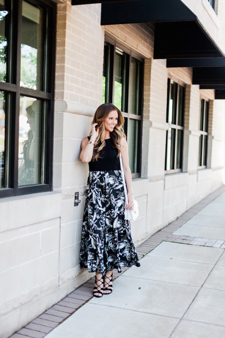 Модель в черном платье с белым тропическим принтом