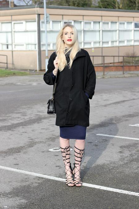 Модель в черной куртке, синее платье футляр и черные сандалии гладиаторы
