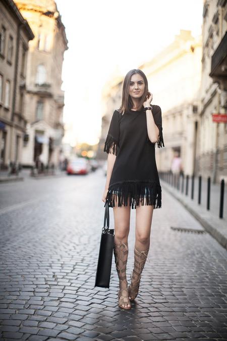 Модель в черной тунике, джинсовых шортах и бежевые сандалии гладиаторы