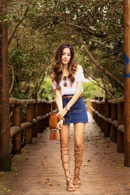 Модель в джинсовой мини юбке, блуза и коричневая сумочка, сандалии гладиатора