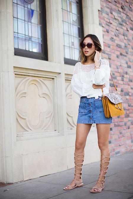 Модель в джинсовой юбке, белая блуза и ежевые сандалии гладиаторы