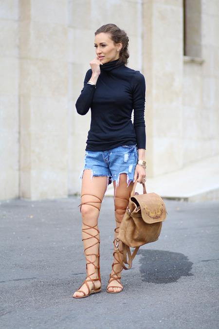 Модель в рваных джинсовых шортах, черная водолазка и сандалии гладиатора