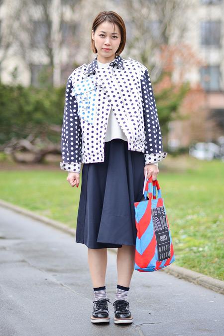 Модель в синей юбке миди, куртка в горошек и красно голубая сумка тоут