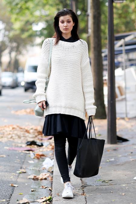 Модель в юбке, белый длиный свитер и черная сумка тоут