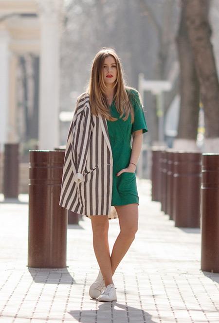Модель в зеленом мини платье и полосатом пиджаке