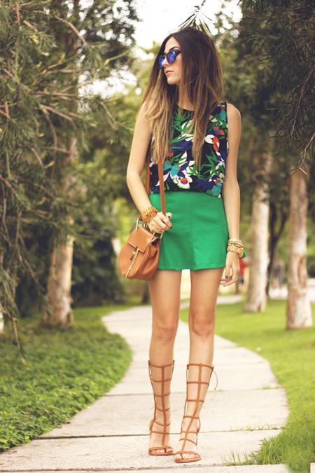 Модель в зеленой мини юбке, цветной топ и коричневые сандалии гладиаторы