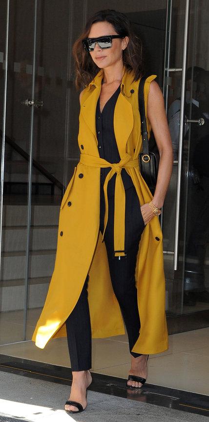 Виктория Бекхэм в черных брюках и длинной желтой жилетке