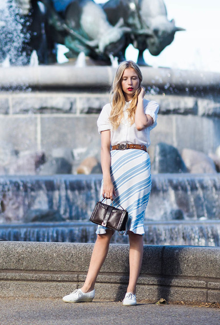 девушка в белой рубашке и узкой юбке с голубую диагональную полоску