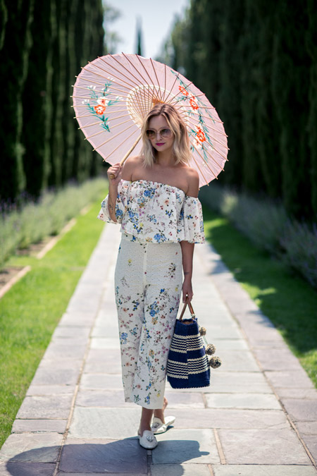 Девушка в белом комбинезоне с мелким принтом, зонтик и шлепанцы