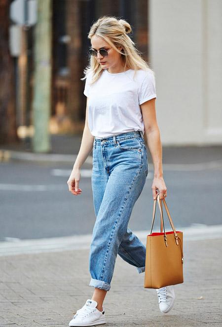 Девушка в белой футболке, голубых джинсах, бежевая сумка тоут и кеды