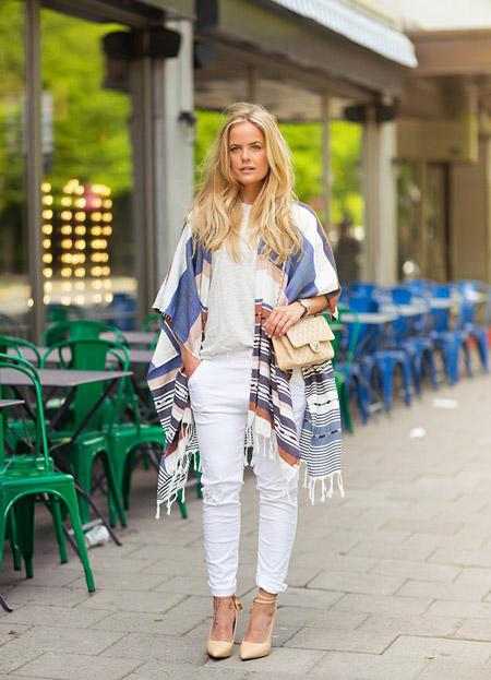 Девушка в белых брюках и пончо