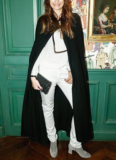 Девушка в белых джинсах, кофте и черной длинной накидке