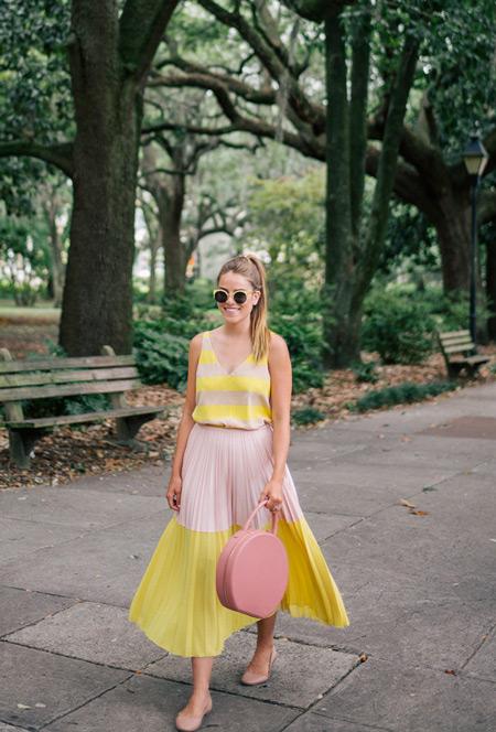 Девушка в бежево-желтом платье и розовой сумочкой