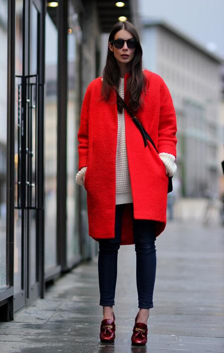Девушка в бежевом свитере и красном пальто