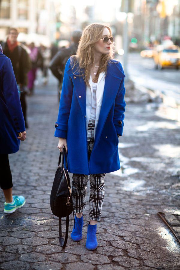 Девушка в брюках в клетку и синем пальто