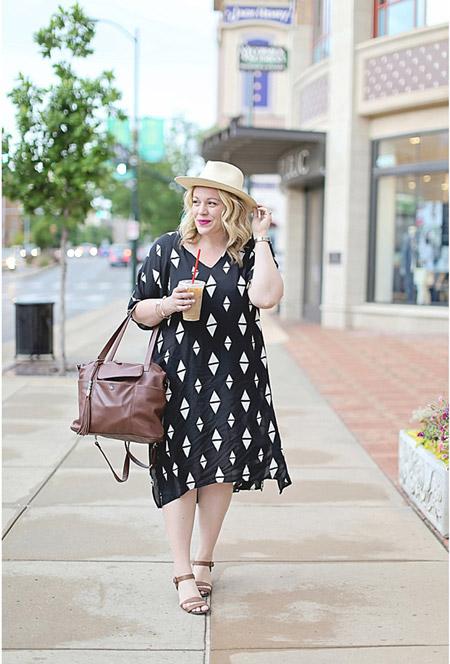 Девушка в черном просторном платье, шляпа и коричневая сумка