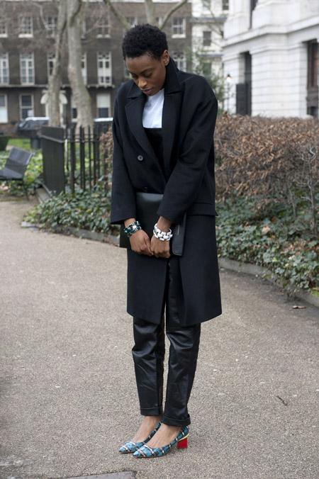 Девушка в черных брюках и пальто чуть выше колена