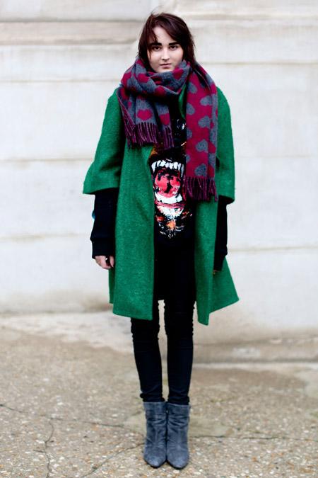 Девушка в черных джеггинсах, кофте, зеленом пальто и серых ботильонах