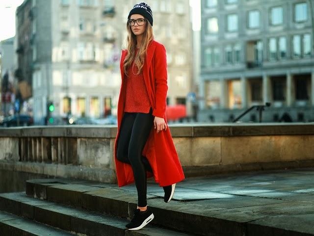 Девушка в черных кроссовках и красном пальто