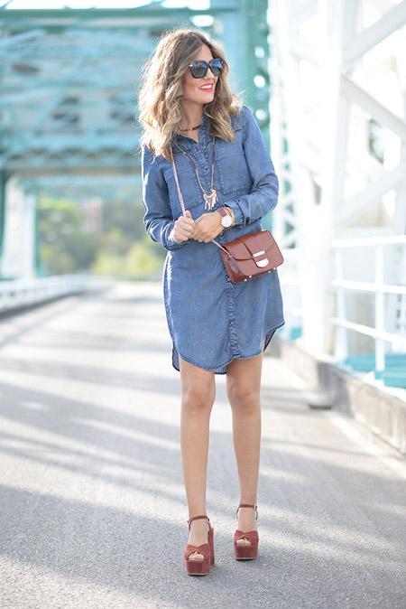 Девушка в джинсовом платье и коричневых босоножках