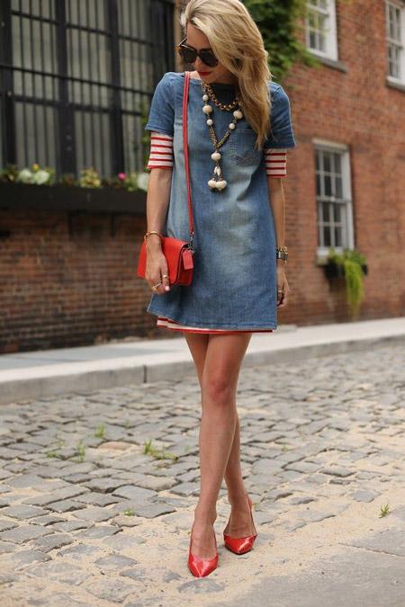 Девушка в джинсовом платье с красной сумочкой